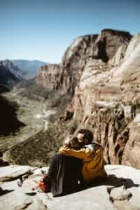 loving couple sitting on a rock